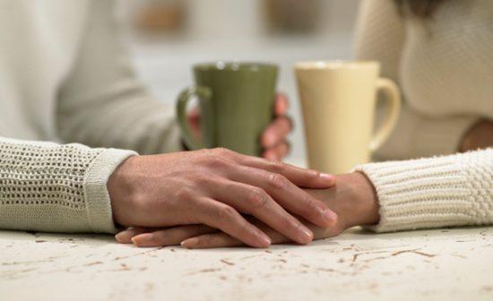 люди пьют чай и держатся за руки